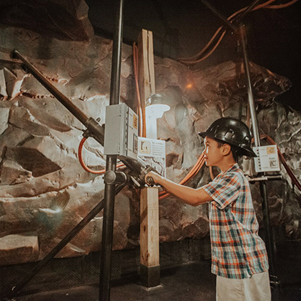 A little boy wearing a hard hat uses a copy of a mining jack hammer.
