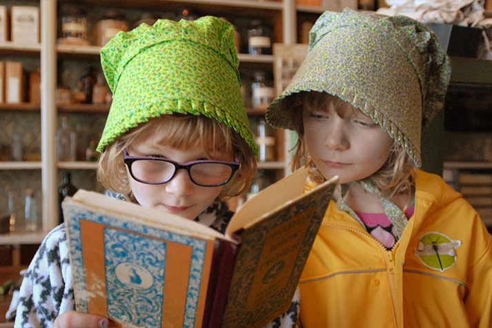 Two girls wearing bonnets read a book together.
