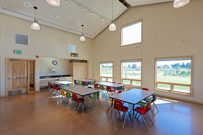 Classroom with tables and chairs and four large windows.