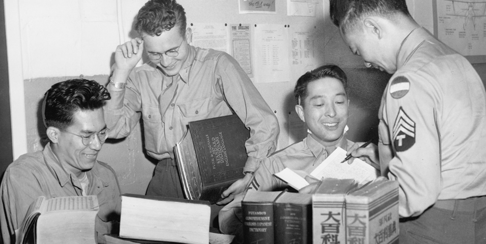 Four men in gathered around a table with books.
