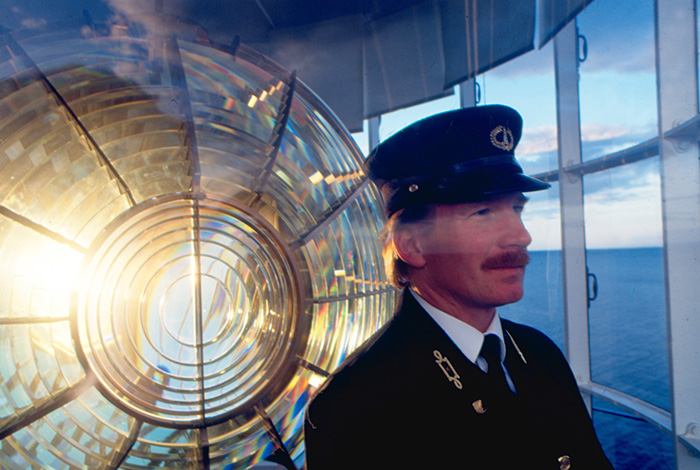 Lightkeeper in front of a lighthouse lens.