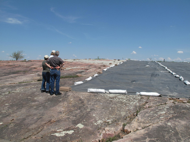 Three people standing beside a covered red rock in the process of lichen removal.