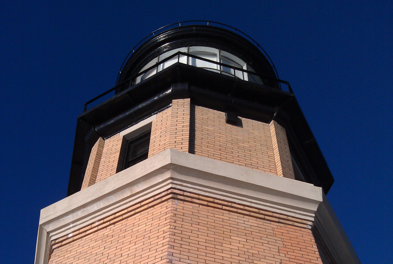 The top of the lighthouse, with a dark blue sky