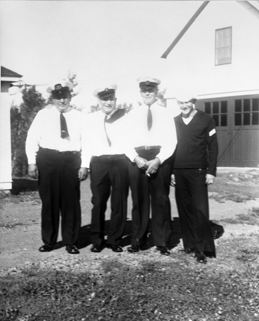 Four lighthouse keepers lined up in uniform