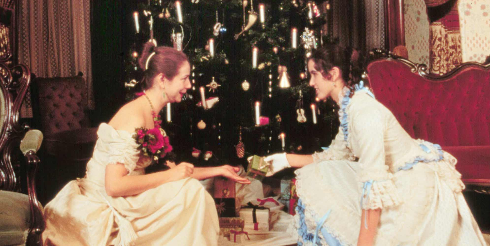 Two women in Victorian dresses sitting in front of a Christmas tree exchanging gifts