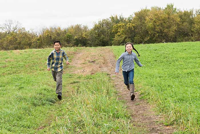 A boy and a girl running on a dirt path toward the camera
