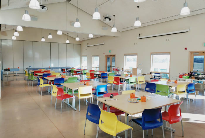 Large room with several square tables and bright colored chairs.