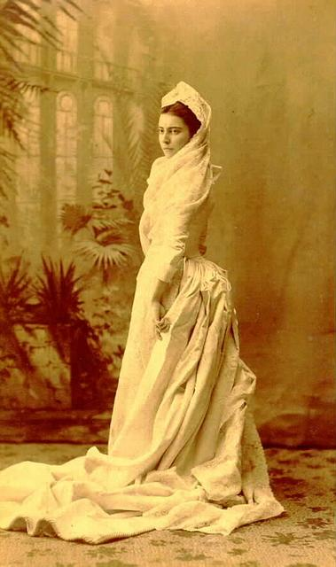 Mamie standing in her wedding dress, facing left