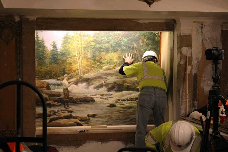 Man cleaning a painting.