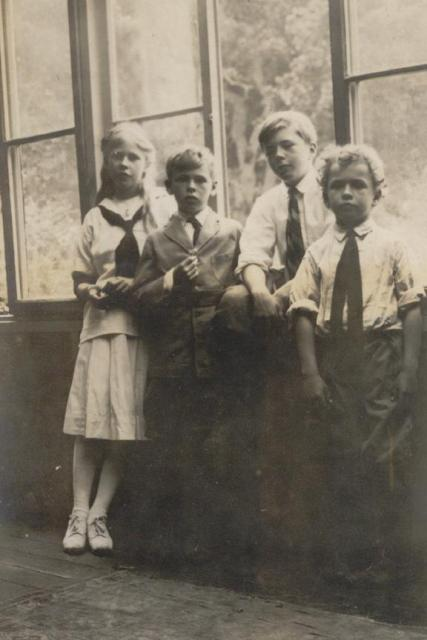 Four children standing in front of windows