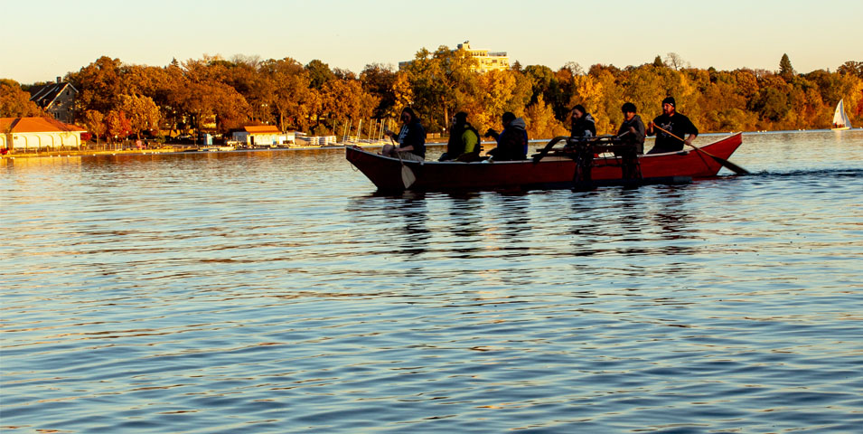 Six people in a canoe on a lake.