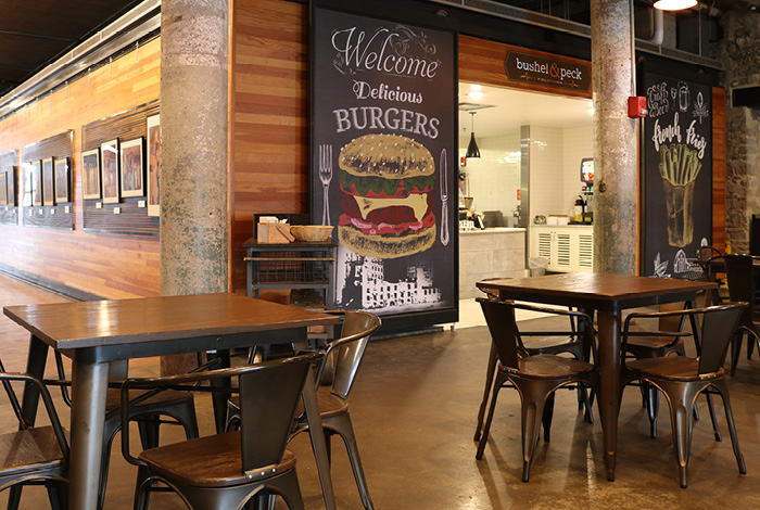 Large chalkboards with colorful chalk drawings flank the entrance to Bushel & Peck café.