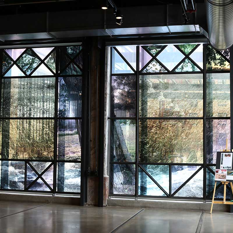 Two large colored glass art installations crossed with steel.