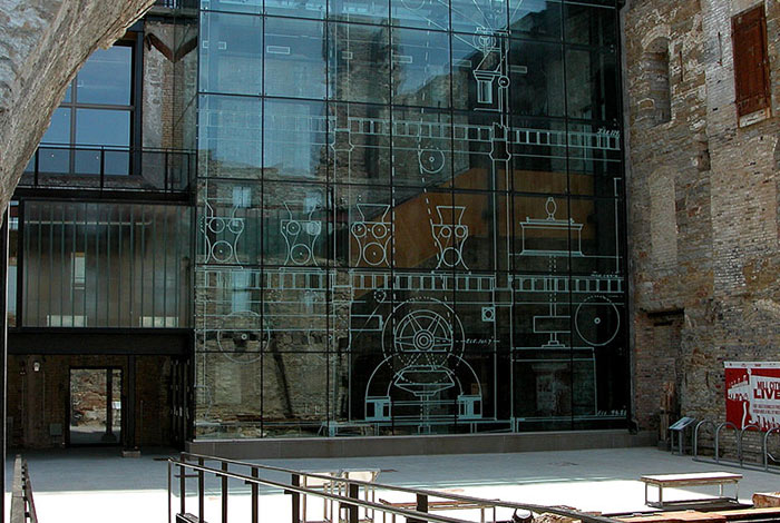 Courtyard with stone and glass wall behind it and seating in front.