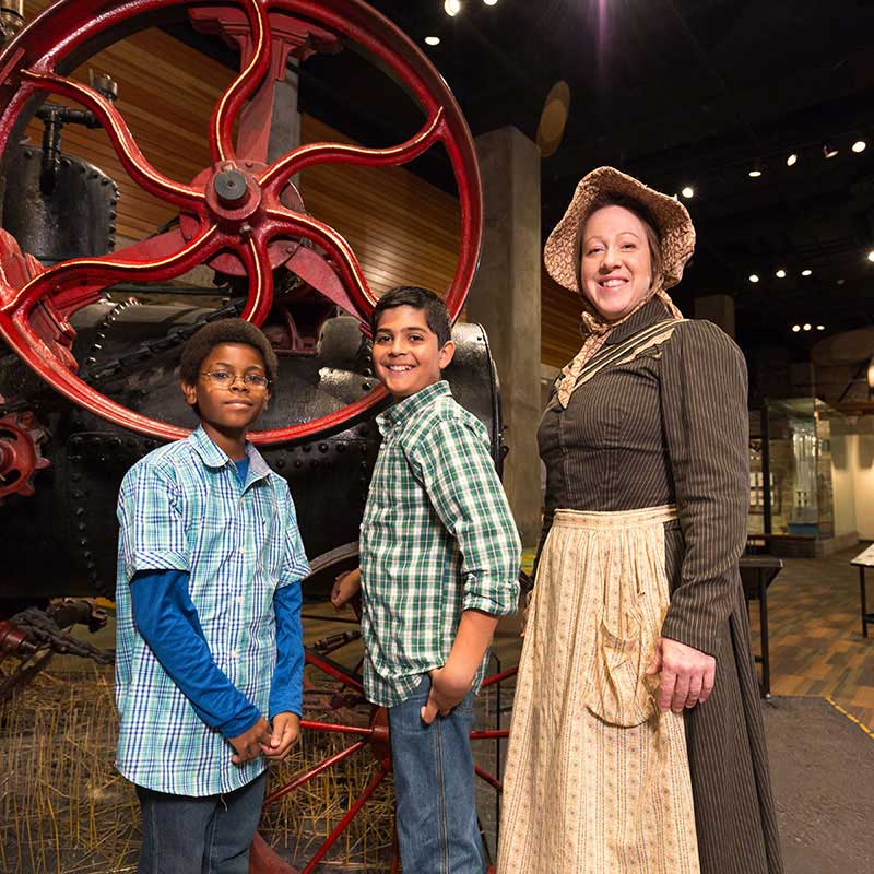 A costumed museum interpreter stands with two boys in the museum gallery.