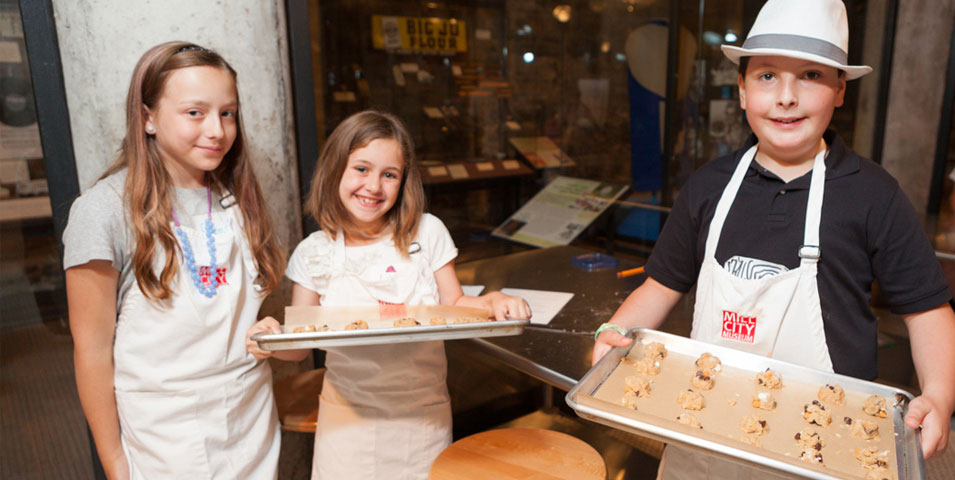 Three kids stand in aprons holding sheets of unbaked cookies.
