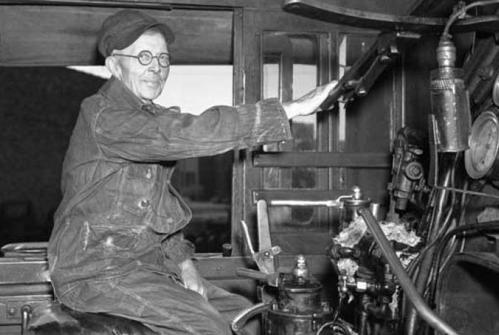 A man operating a train, black and white photo.