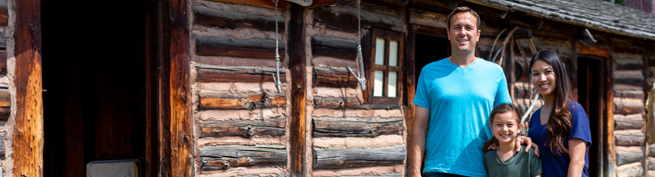 A family standing in front of a log cabin.