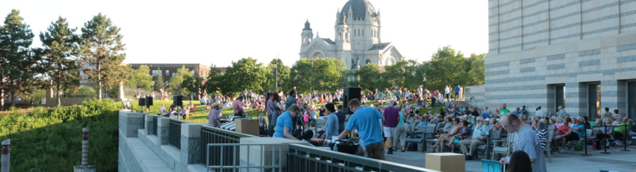 A crowd gathered outside of the Minnesota History Center on a summer day.