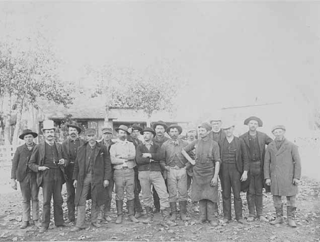 Historic photo of several men standing in a line, all in various work attire. Source: MNHS Collections.