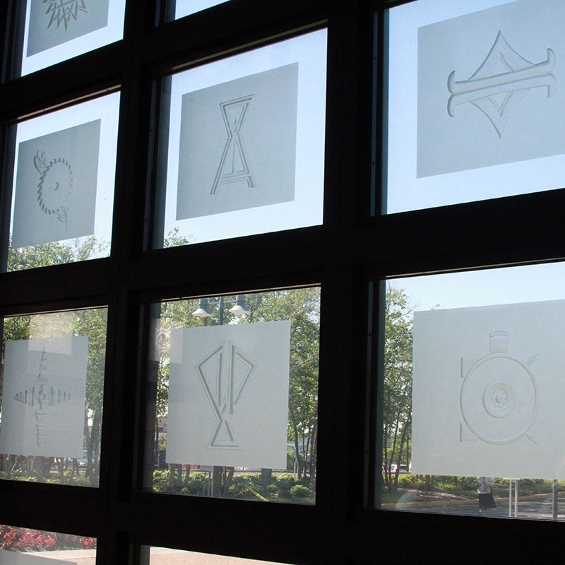 A group of glass etchings in a window grid.