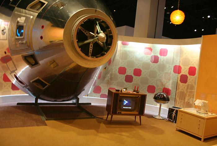 A replica Apollo 8 Command Module sits next to an antique box television.