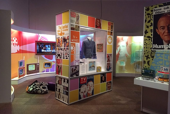 "Colorful panels and images surround an exhibit displaying a sweater and shoes from the show ""Mister Rogers' Neighborhood."""