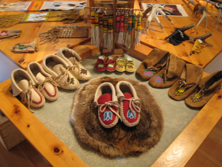 Moccasins and other Indian crafts are displayed tidily on a wood table.