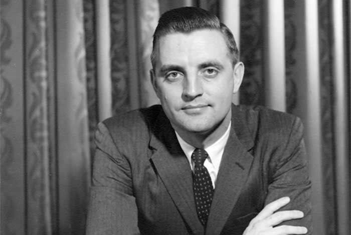 Photograph of Walter Mondale with arms crossed looking at camera.