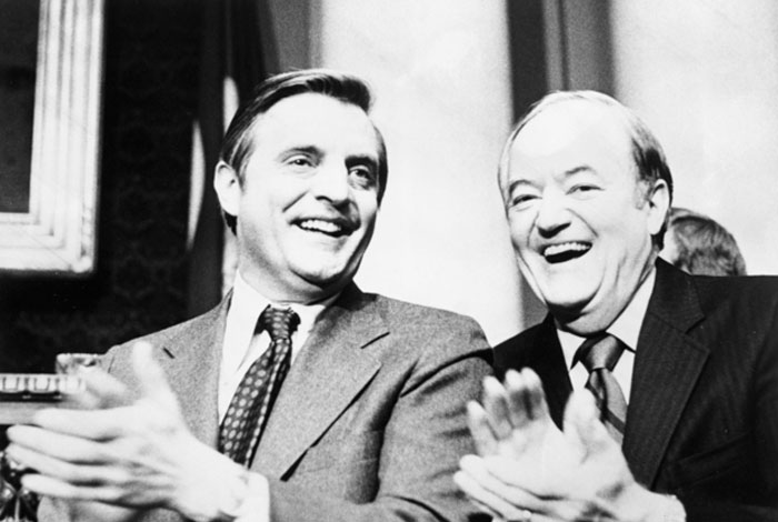 Walter Mondale and Hubert H. Humphrey sitting and clapping.