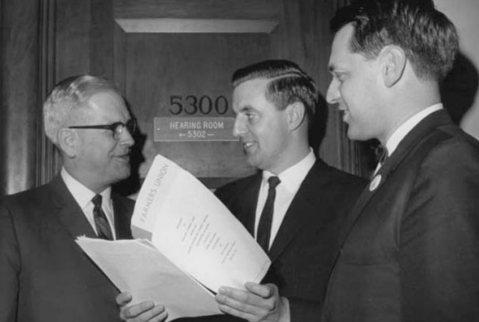 Minnesota Farmers' Union president Ed Christianson, Senator Walter Mondale and Dr. Blue Carstenson of the National Farmers' Union stand together looking over papers.
