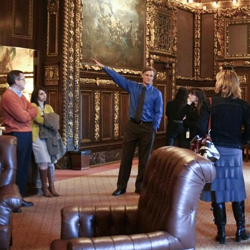 A guide pointing at one of the paintings in the Governor's Reception Room.
