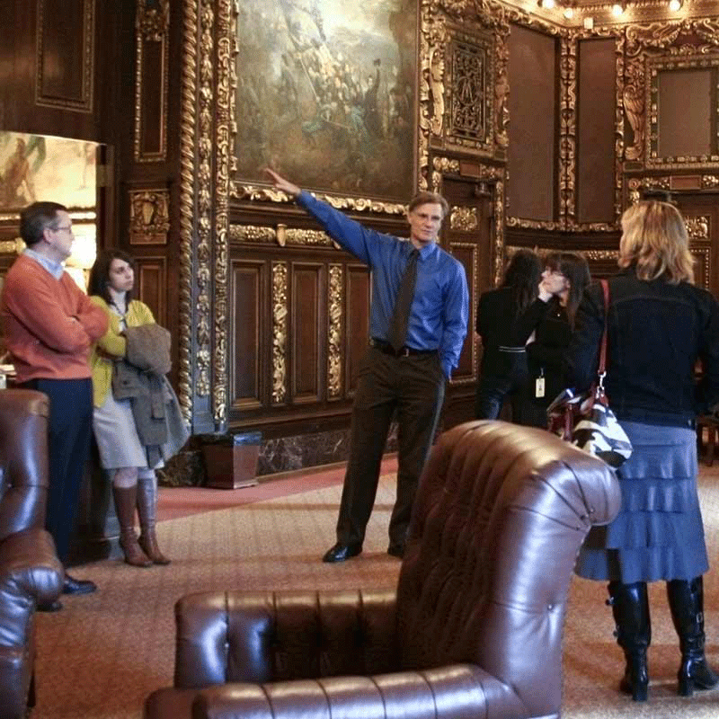 A guide pointing at one of the paintings in the Governor's Reception Room