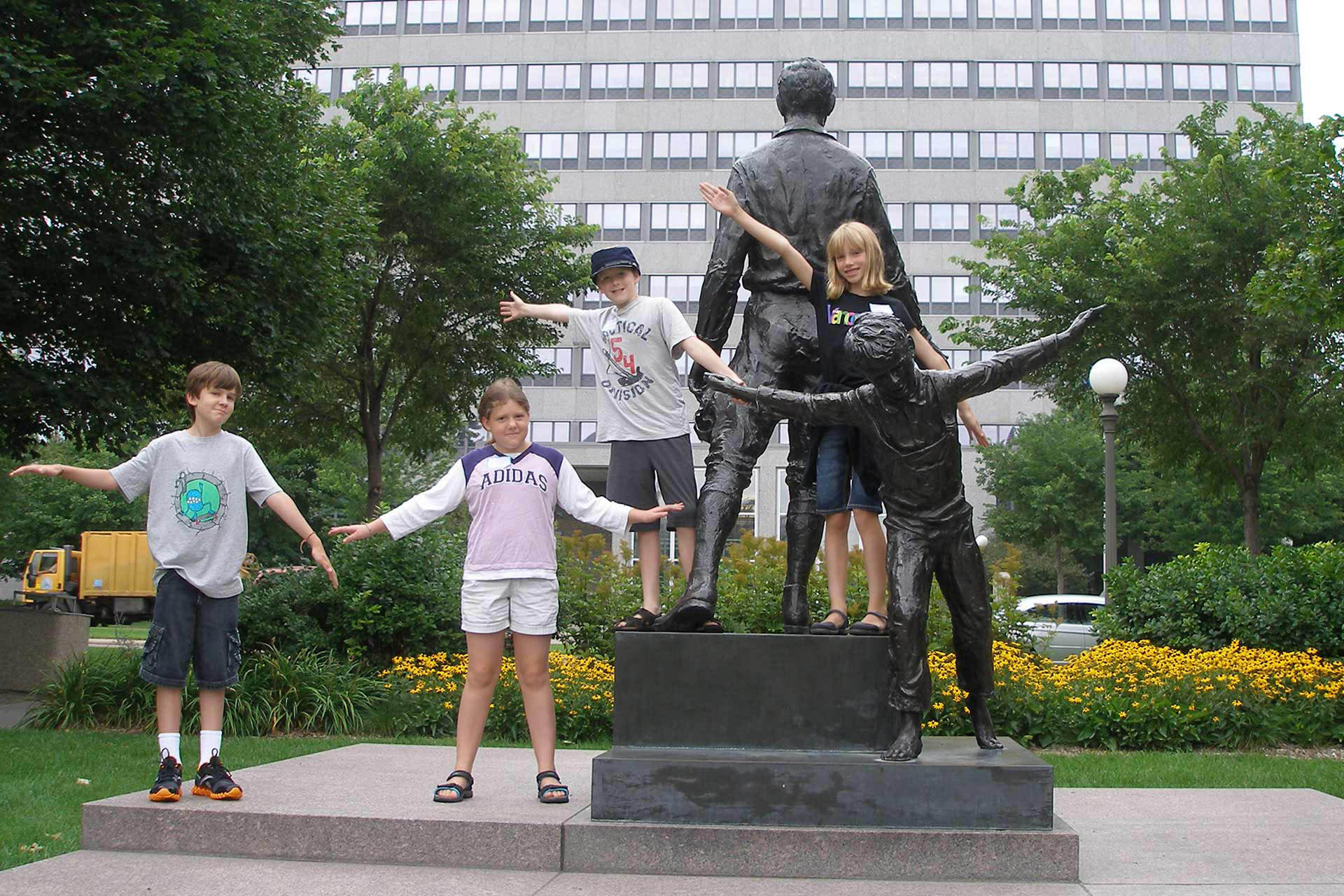 Children posing next to a statue on the Capitol mall