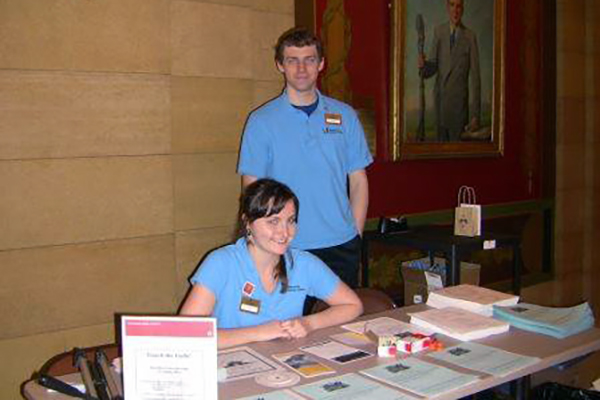 Boy standing behind girl sitting at table with pamphlets and brochures