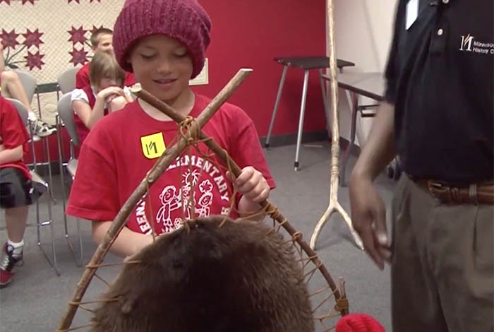 Student examining a fur pelt.