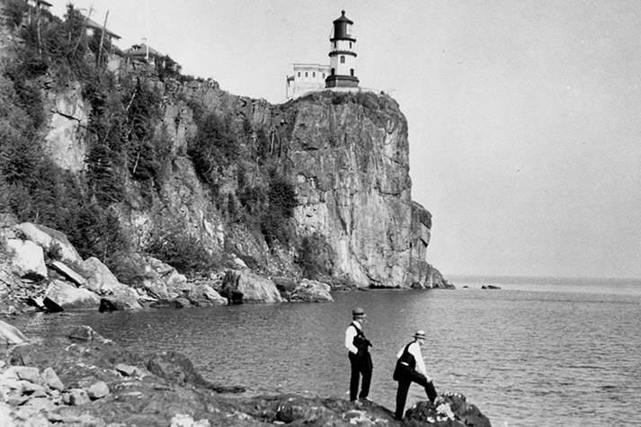 Two men on rocks at the lake's edge with the cliff and lighthouse in the background