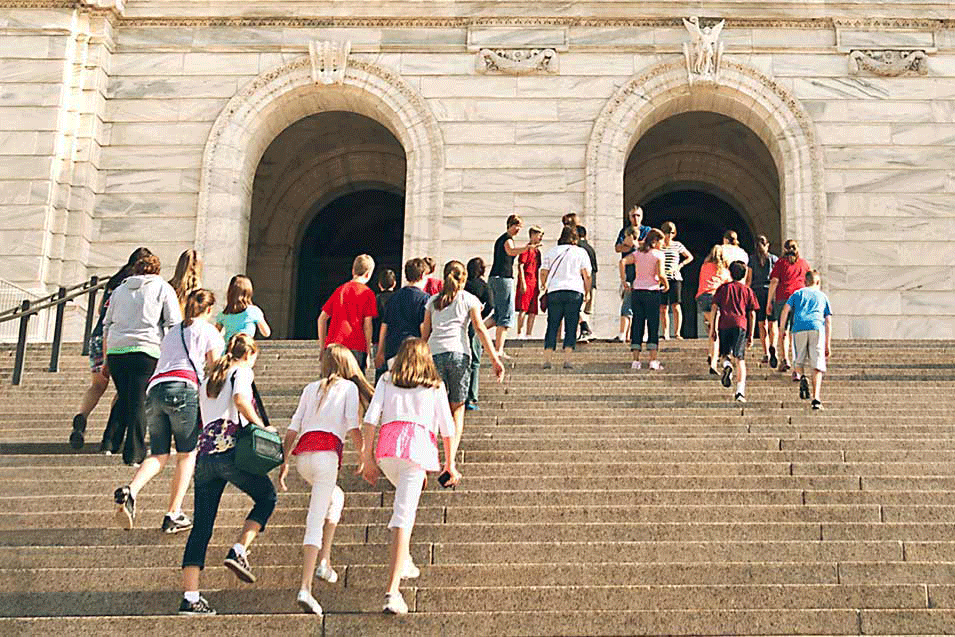 Many people walking up stairs to the Capitol entrance