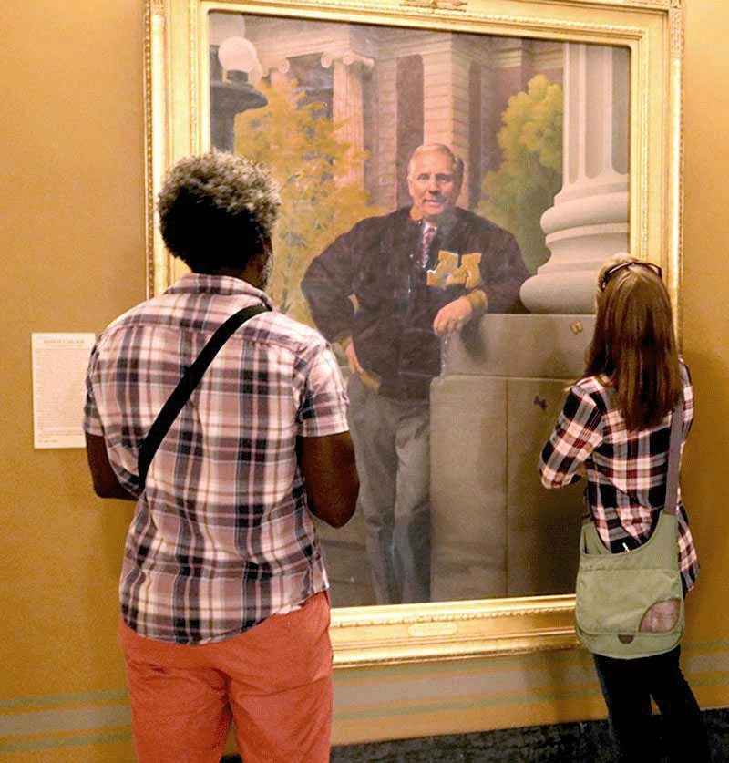 Two people looking at Gov. Carlson's portrait.