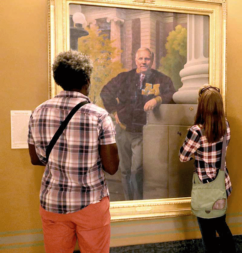 two people looking at Gov. Carlson's portrait