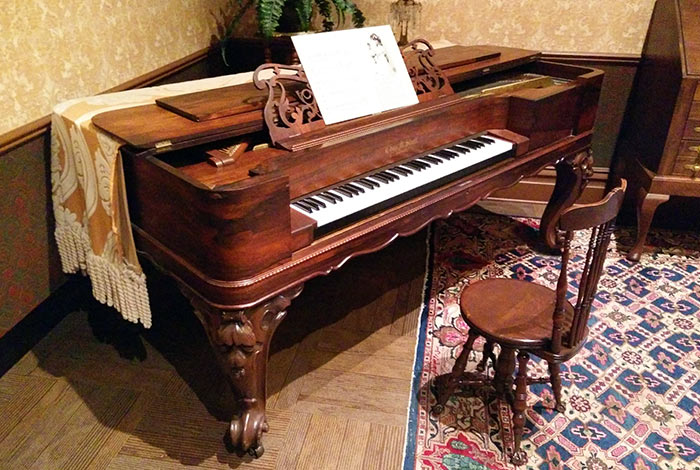 A baby grand piano with sheet music on it.