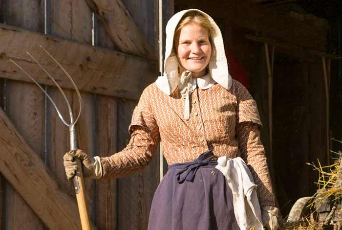 A woman with a pitchfork in a barn