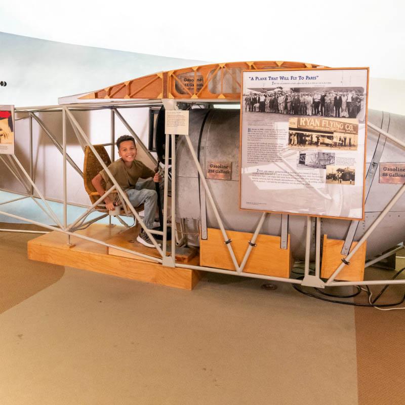 Boy sitting in an airplane replica.