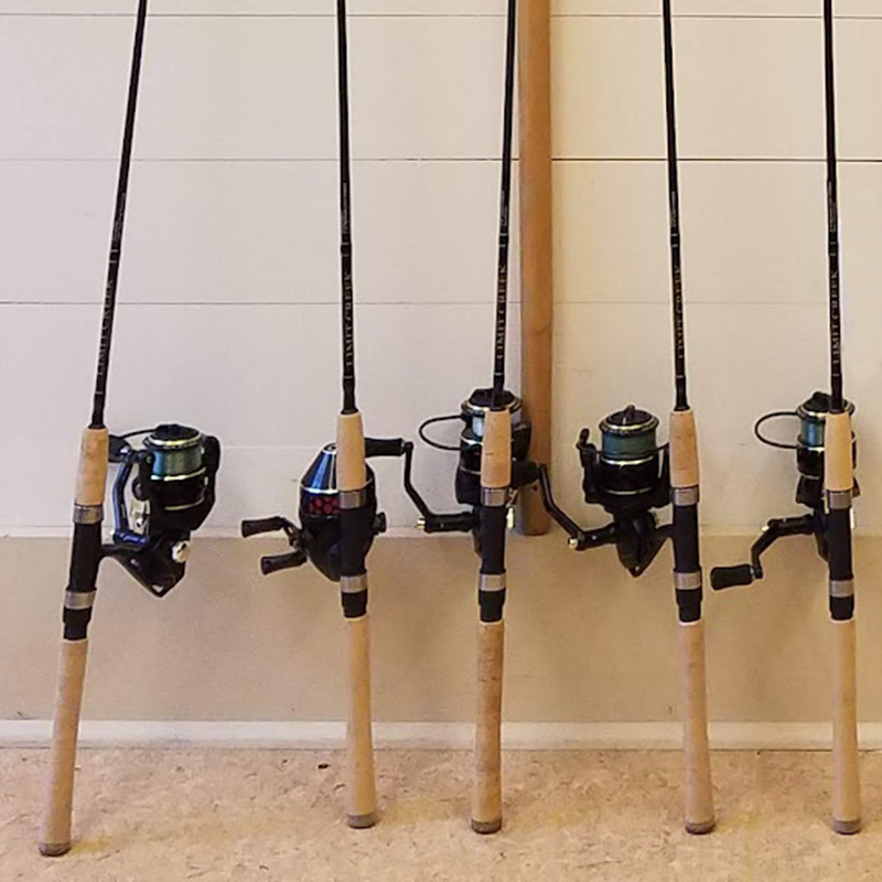 Fishing poles leaning against a wall.