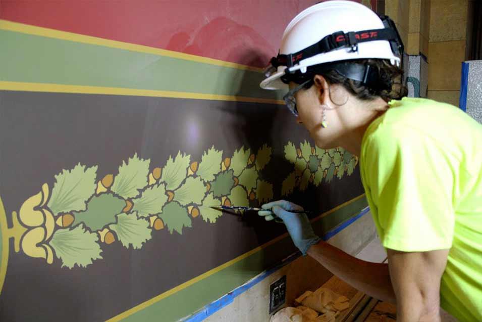 A conservator restoring a mural