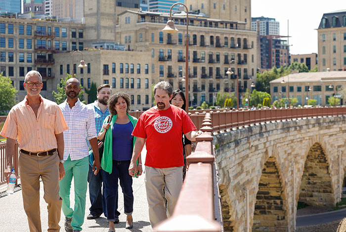 Group of people walking across the Stone Arch Bridge.