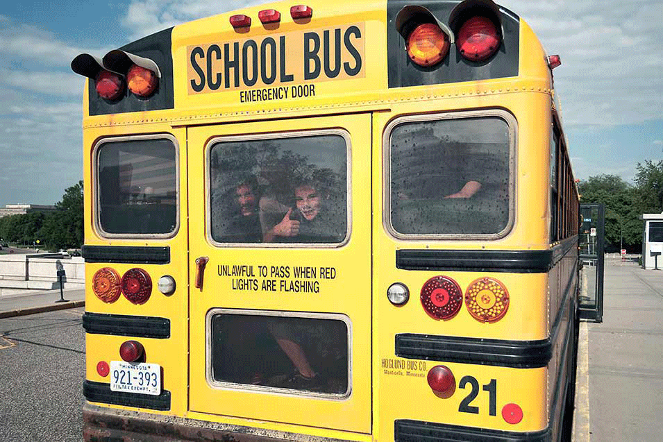 School children looking out the back window of a school bus