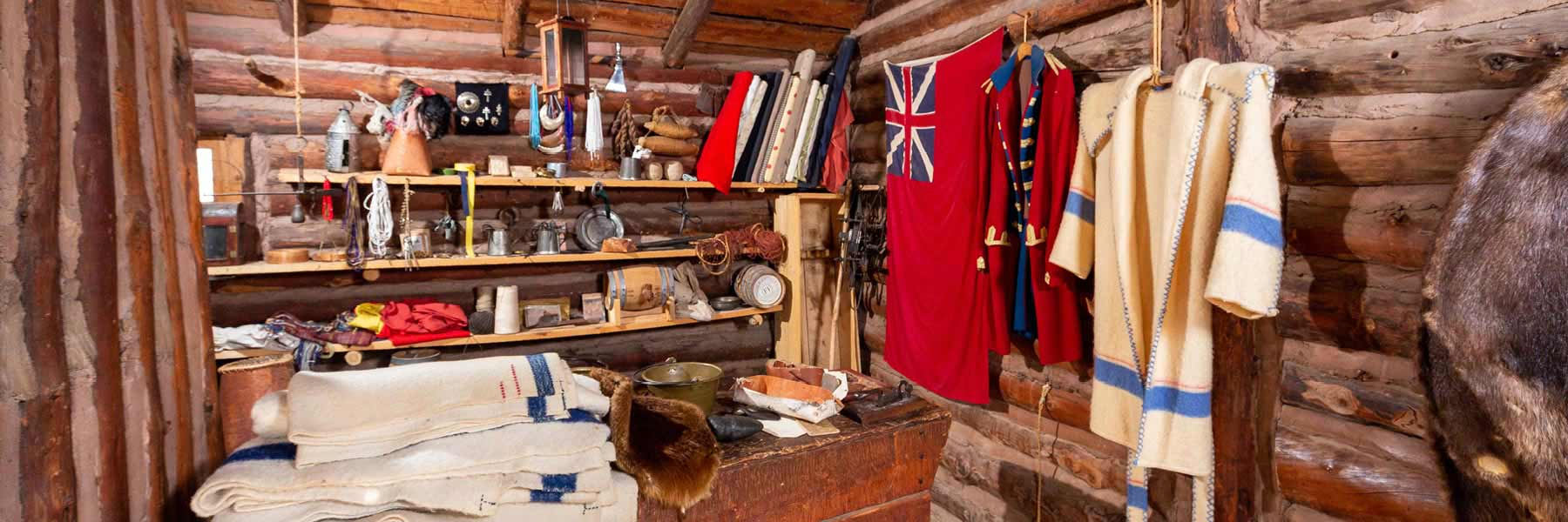 A log cabin interior decorated with late 18th century artifacts including a British flag.