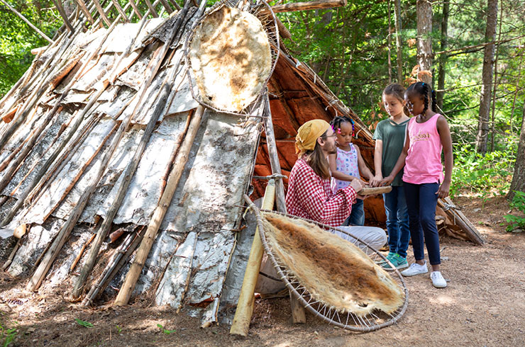 Children talking to a guide who is seated in a birch bark shelter.