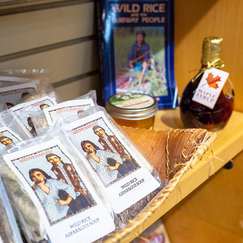 A store display containing maple syrup, jams, and wild rice soup.